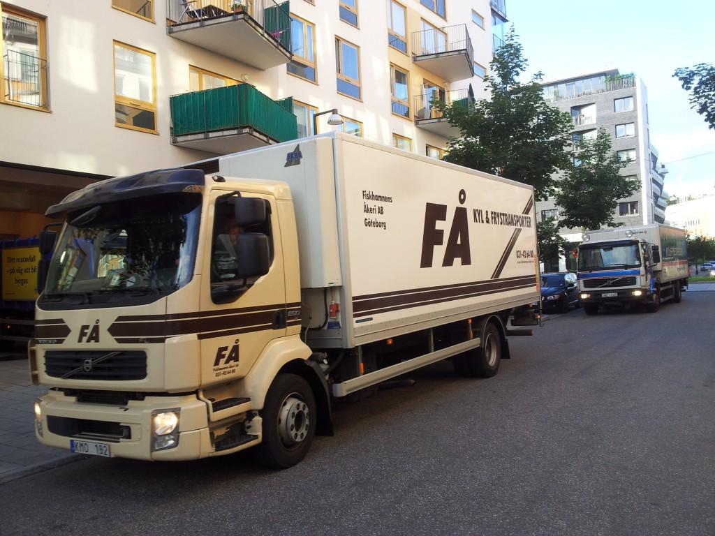 Kö med lastbilar som ska lossa varor på liten stadsgata